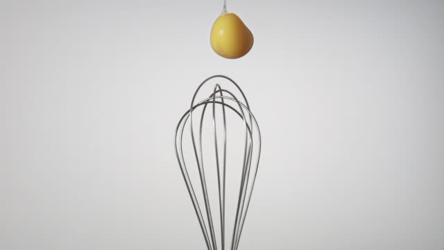 cu slo mo shot of egg yolk getting smashed while falling into spinning eggbeater / munich, bavaria, germany - studio shot stock videos & royalty-free footage