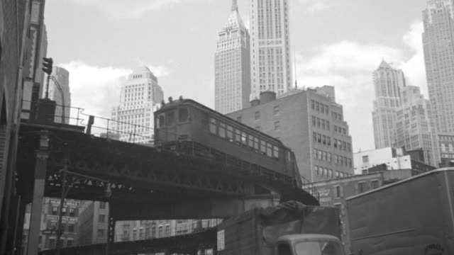 MS Shot of EL train moving on bridge in front of New York city buildings