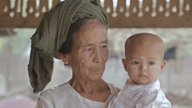 ms shot of elderly woman holding baby with thanaka (sunscreen) on its face / bagan, mandalay division, myanmar - pagan stock-videos und b-roll-filmmaterial