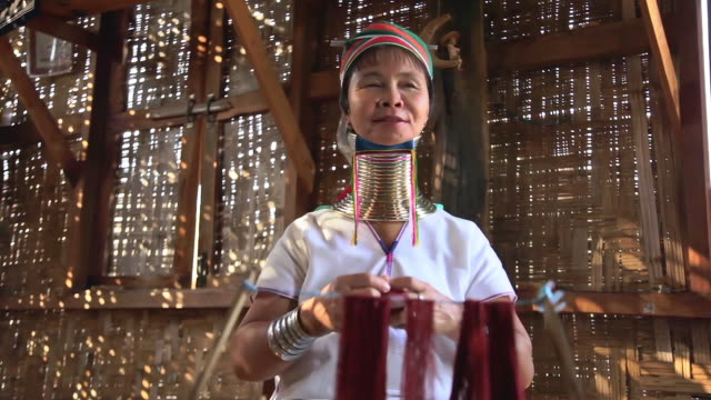 stockvideo's en b-roll-footage met ms la shot of elderly woman wearing neck rings weaving on loom / inle lake, shan state, myanmar   - werkende bejaarden