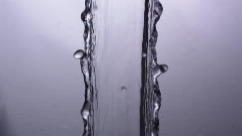 cu slo mo shot of elegant stream of water falling through frame / united kingdom - flowing stock videos & royalty-free footage