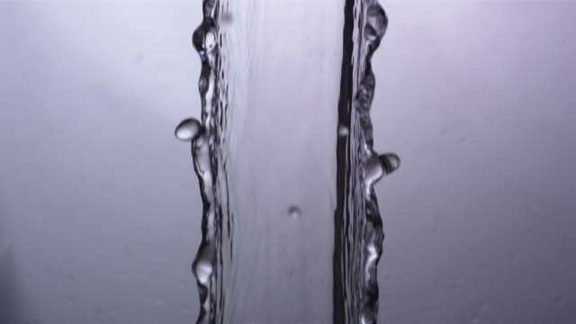 CU SLO MO Shot of elegant stream of water falling through frame / United Kingdom