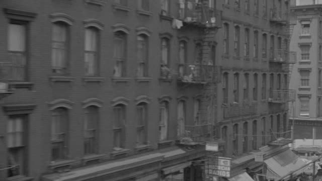 MS POV Shot of elevated train traveling through tenement district passing apartment buildings