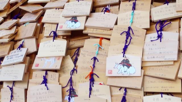 ms pan shot of ema, small wooden plaques, at yushima shrine / tokyo, japan - 飾り板点の映像素材/bロール
