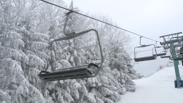 ms pov shot of empty chairs going in opposite direction on chairlift  / ellicottville, new york, united states  - seggiovia video stock e b–roll