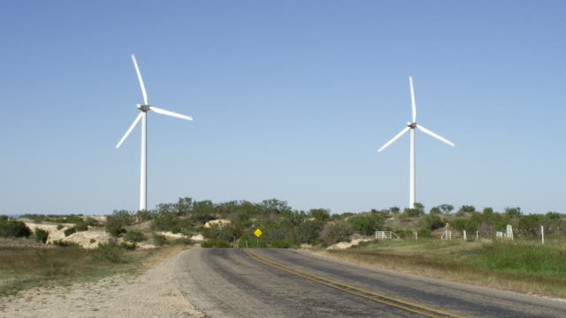 MS Shot of empty two lane highway with two wind turbines / Texas, United States