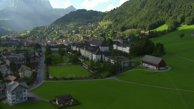 ms aerial shot of engelberg monastery and village with lake eugenisee and valley engelberge / engelberg, obwalden, switzerland - 村点の映像素材/bロール