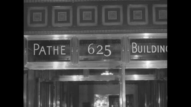 shot of entrance to pathe building / executives sitting in film projection room waiting to watch film, film projector starts running and lights are... - proiettore cinematografico video stock e b–roll
