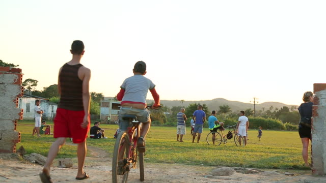 MS shot of Entrance to soccer field and Children playing soccer in Small town / Cuba