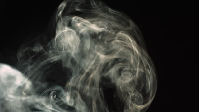 CU SLO MO Shot of entrancing coils of smoke rising through frame