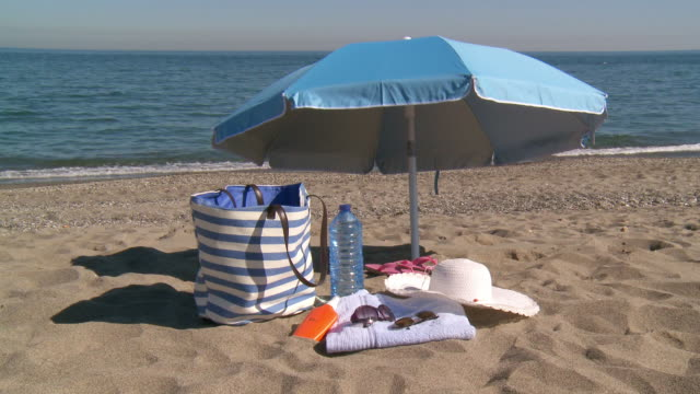 ms shot of essentials for day under sun on beach / marbella, andalusia, spain - oggetto creato dall'uomo video stock e b–roll