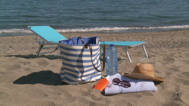 ms shot of essentials for day under sun on beach / marbella, andalusia, spain - sonnencreme stock-videos und b-roll-filmmaterial