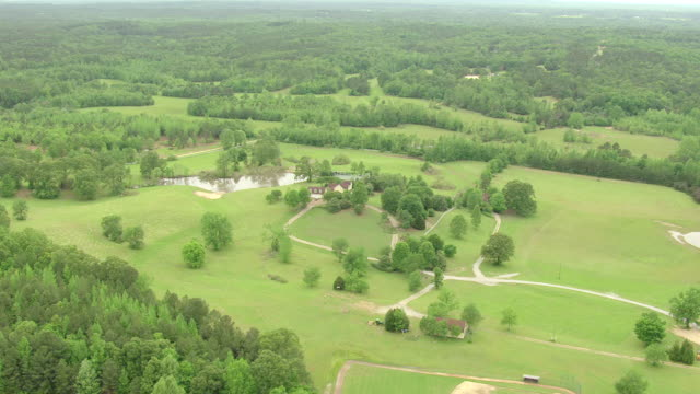 WS AERIAL TD Shot of estate of John Grisham Estate and surrounding landscape with pond / Oxford, Mississippi, United States