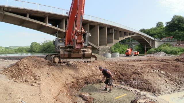 ws shot of excavator immersing construction material into saar river / wiltingen, rhineland palatinate, germany - construction material stock videos and b-roll footage