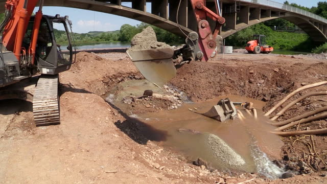 ms shot of excavator immersing construction material into saar river / wiltingen, rhineland palatinate, germany - construction material stock videos & royalty-free footage