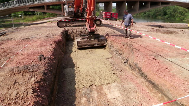 ms shot of excavator leveling material in pit at bridge construction site at saar river, wiltingen, germany / wiltingen, rhineland palatinate, germany - pit mine stock videos and b-roll footage
