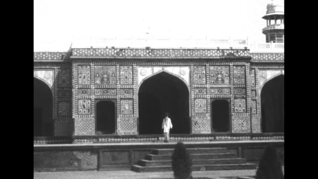 shot of exterior of building / two shots of men walking through formal garden in lahore india / shot through archway of garden and building / man... - imperium bildbanksvideor och videomaterial från bakom kulisserna