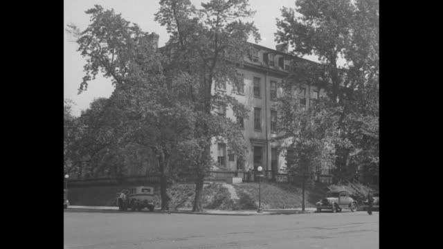 shot of exterior of the old brick capitol, with trees in front and cars parked on street; the house stands on a corner / man standing in front of... - ジェームス モンロー点の映像素材/bロール