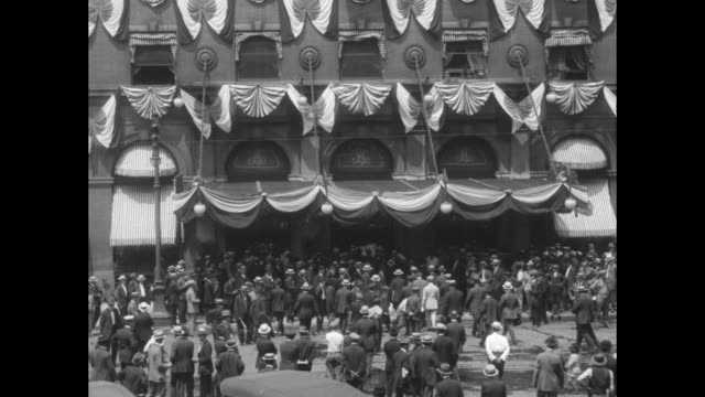 Shot of exterior of the St Louis Coliseum decorated with flags crowd milling around in front of hall / leader of Tammany Hall Charles Francis Murphy...
