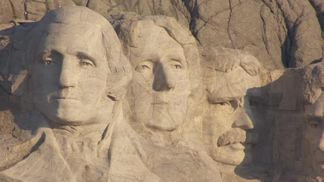 ms aerial ts pan shot of face details of abraham lincoln and theodore roosevelt and thomas jefferson and george washington at mount rushmore / south dakota, united states - präsident der usa stock-videos und b-roll-filmmaterial