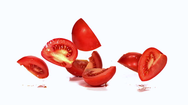 MS SLO MO Shot of falling red tomatoes(solanum lycopersicum) cutted fruits / Vieux Pont, Normandy, France