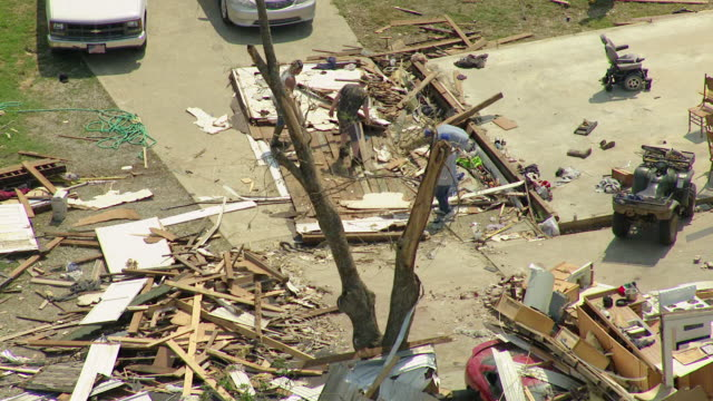 MS AERIAL Shot of family picking through ruined home / Smithville, Mississippi, United States
