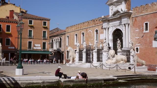 WS Shot of family sitting on bund near Portale dell' Arsenale / Venice, Veneto, Italy