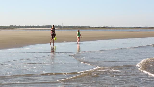 vídeos de stock, filmes e b-roll de ws shot of family walking on beach and sea waves at coast / st simon's island, georgia, united states - tempo real