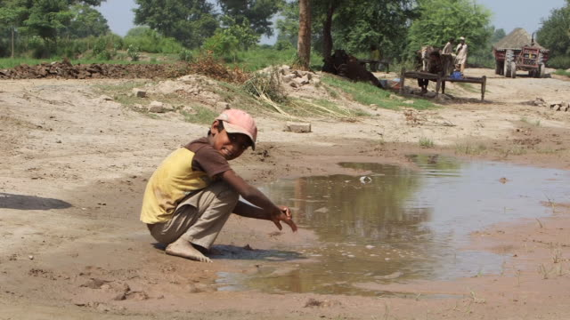 vidéos et rushes de shot of family washing their hands in open street water / old city of lahore, punjab, pakistan - province du panjab