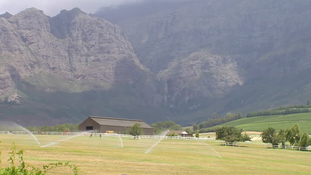 ws shot of farm in front of majestic mountains / south africa - paarl stock videos & royalty-free footage
