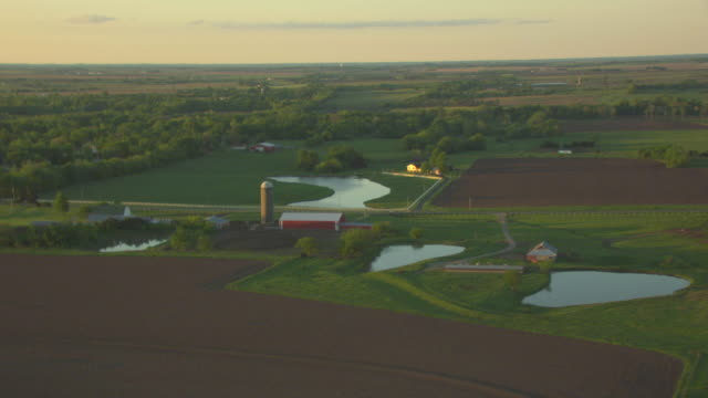 ws aerial shot of farm land with red barn and silo in franklin county during sunrise / kansas, united states - barn stock videos & royalty-free footage