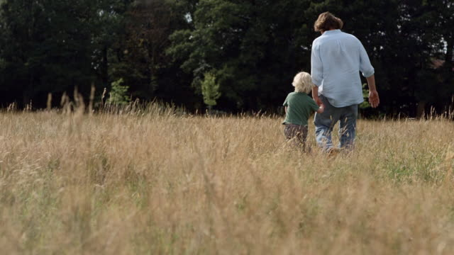 MS SLO MO Shot of father and son holding hands walking through field