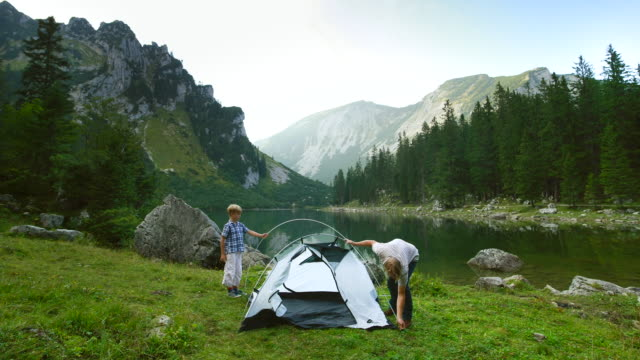 """ms t/l shot of father and son pitching tent at lakeside """"soinsee"""" in alpine mountains / bayrischzell, bavaria, germany - tent stock videos & royalty-free footage"""