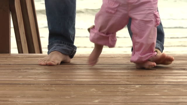 ms ts shot of father helps his daughter stand up to practice walking / manistique, michigan, united states - erste schritte stock-videos und b-roll-filmmaterial