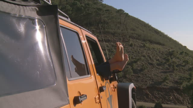 MS Shot of feet sticking out of off road vehicle in mountains, woman relaxing / Tolox, Andalusia, Spain