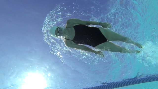 MS PAN SLO MO Shot of female, baby boomer, swimmer performs flip turn in underwater / Davis, California, United States