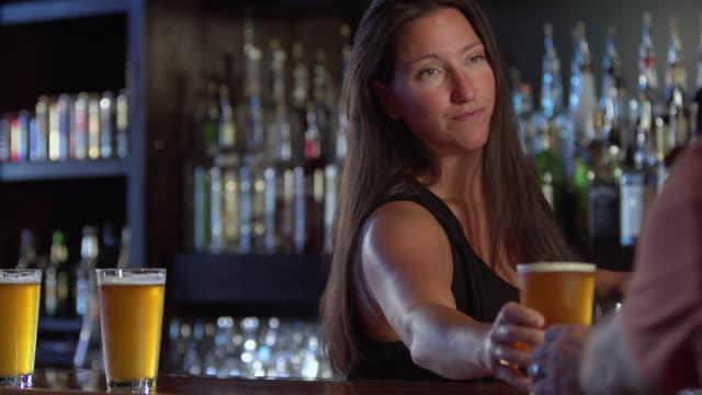 ms slo mo shot of female bartender serving beer / seattle, washington, united states - bartender stock videos & royalty-free footage