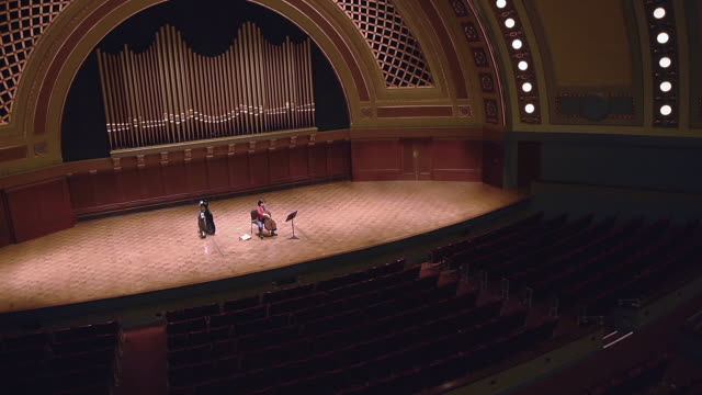 ws tu shot of female cellist practicing solo piece on stage in empty concert hall audio / ann arbor, michigan, united states - concert hall stock videos and b-roll footage