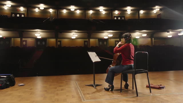 ws shot of female cellist practicing solo piece on stage in empty concert hall audio / ann arbor, michigan, united states - adult stock videos & royalty-free footage