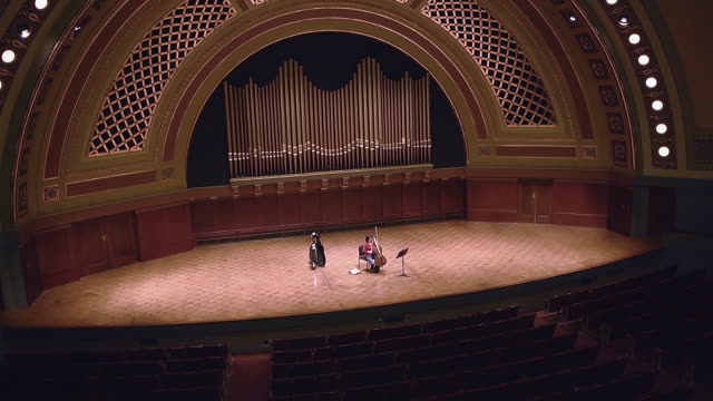 ws shot of female cellist tuning her instrument on stage in empty concert hall audio / ann arbor, michigan, united state - adult stock videos & royalty-free footage