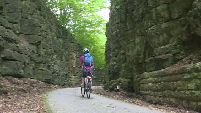 vidéos et rushes de ms ts shot of female cyclist passing through cliff at forest area / echternach, luxembourg - grand duché du luxembourg