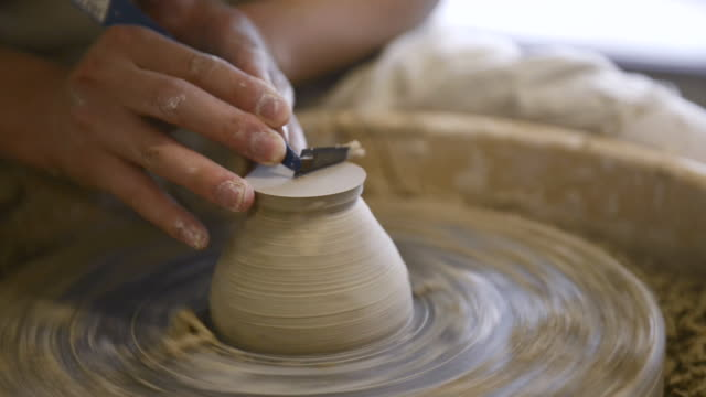 cu shot of female potter are sharpened bowl with pottery wheel in studio / kyoto, japan - potter's wheel stock videos & royalty-free footage