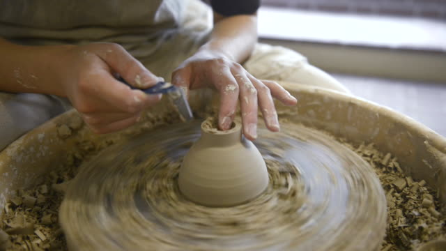 cu shot of female potter are sharpened bowl with pottery wheel in studio / kyoto, japan - art and craft stock videos & royalty-free footage