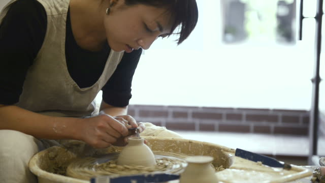 ms shot of female potter are sharpened bowl with pottery wheel in studio / kyoto, japan - pottery stock videos & royalty-free footage