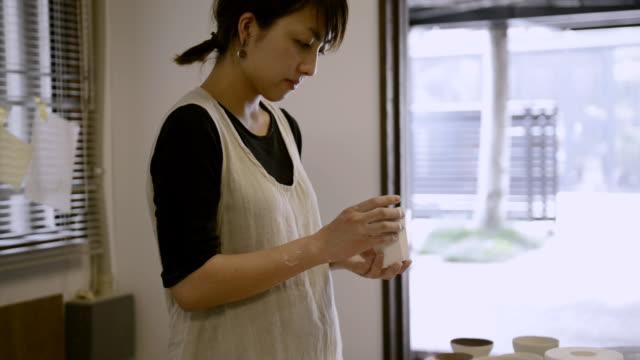 MS TD Shot of female potter confirm wooden bowl in studio / Kyoto, Japan