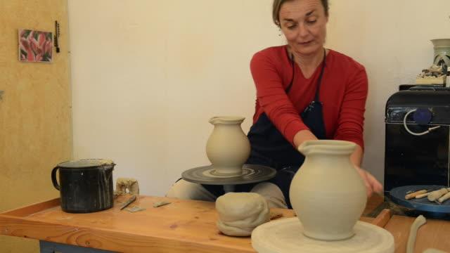 ms shot of female potter finishing and put away pitcher on potterwheel at pottery / landshut, bavaria, germany - pitcher jug stock videos & royalty-free footage
