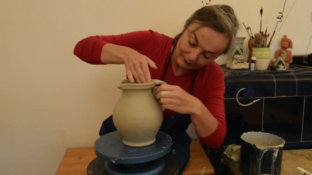 ms shot of female potter finishing and smoothing out pitcher on potterwheel at pottery / landshut, bavaria, germany - pitcher jug stock videos & royalty-free footage