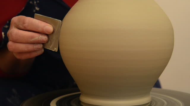 cu tu shot of female potter finishing shaping and smoothing out pitcher on potterwheel at pottery / landshut, bavaria, germany - pitcher jug stock videos & royalty-free footage