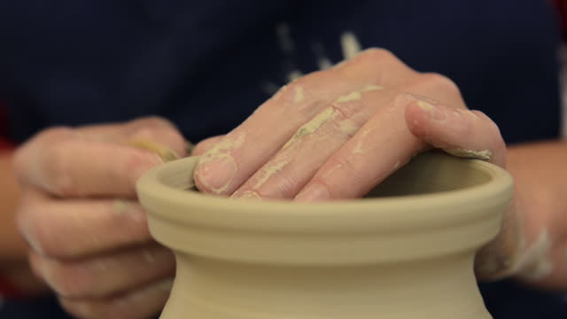 cu shot of female potter finishing shaping pitcher on potterwheel at pottery / landshut, bavaria, germany - potter stock videos & royalty-free footage