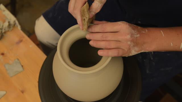 cu shot of female potter finishing shaping pitcher on potterwheel at pottery / landshut, bavaria, germany - pitcher jug stock videos & royalty-free footage